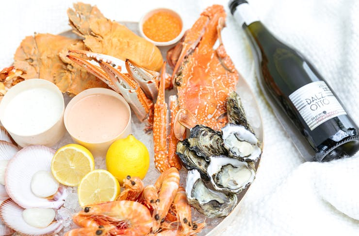 A platter of seafood on ice and a bottle of wine.