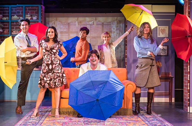 Three actors dressed as the characters from Friends, holding umbrellas and standing on a stage.