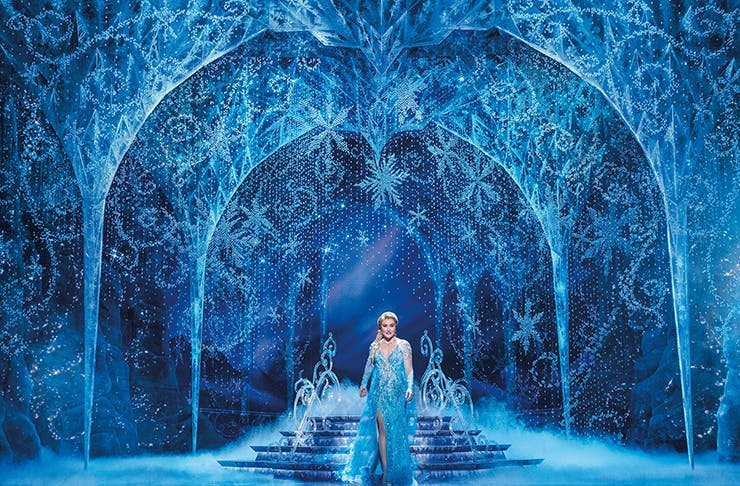 Elsa of Frozen the Musical standing under ice arches.