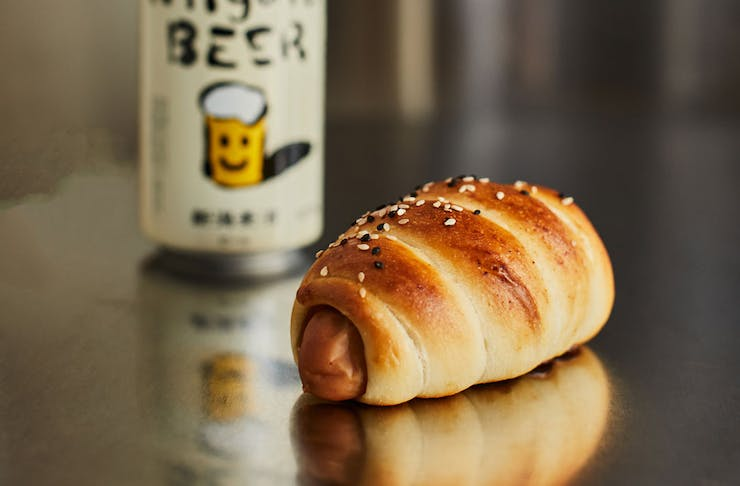 A Japanese-style sausage roll on a surface with a can of Japanese beer.