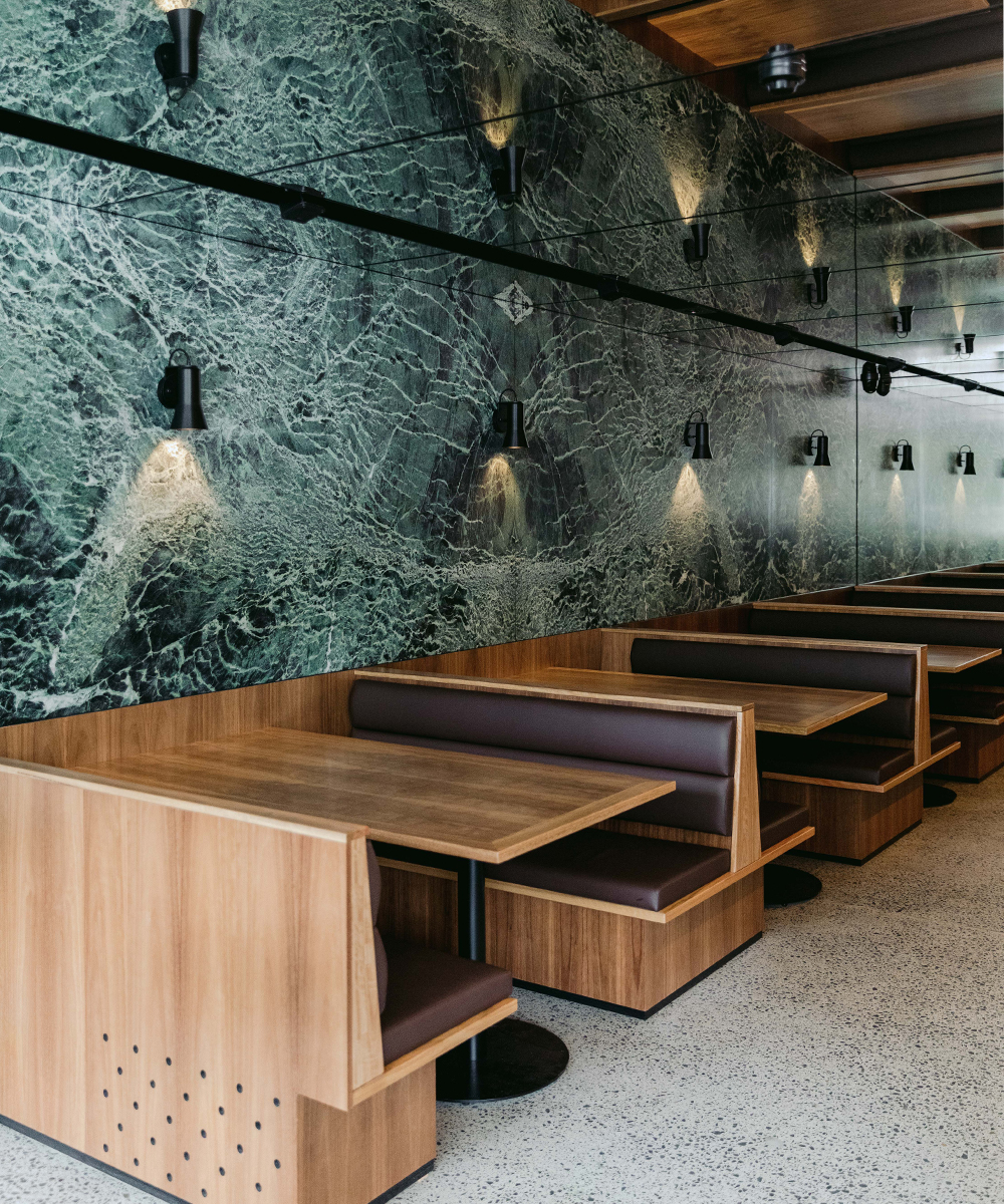 booth tables inside a bar with green marble walls