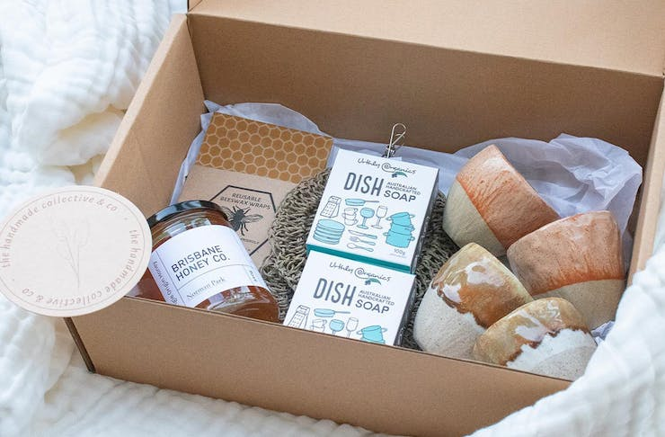 A gift box made of cardboard filled with ceramic mugs, hand made soap and other gift items