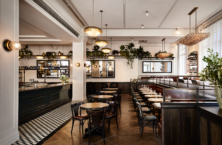 Gimlet's dining area, lined with wood-finished tables and a chequered tile floor.,
