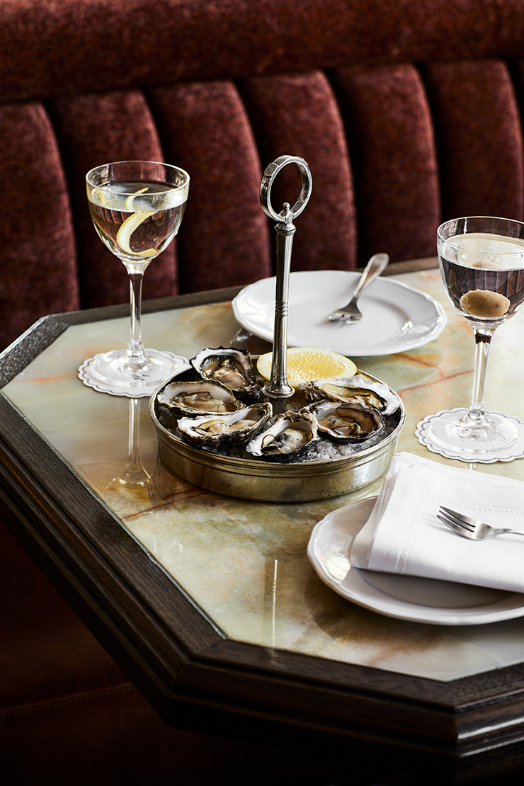 A silver plate holding oysters and surrounded by cocktails garnished with citrus peel.
