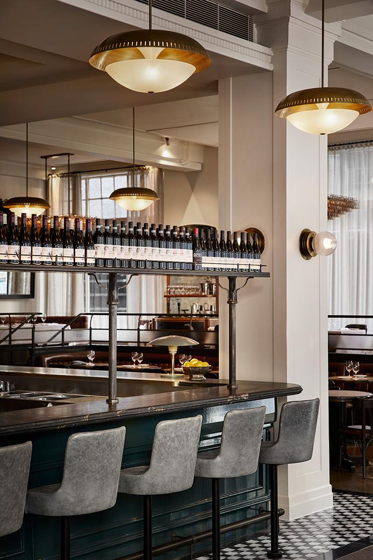 Stone seats up against Gimlet's ornate bar. Wine racks hang overhead.