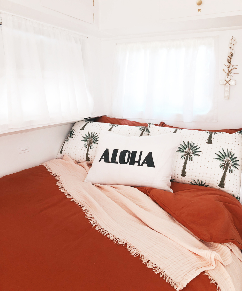 a bed made up wth pretty pillows in a caravan