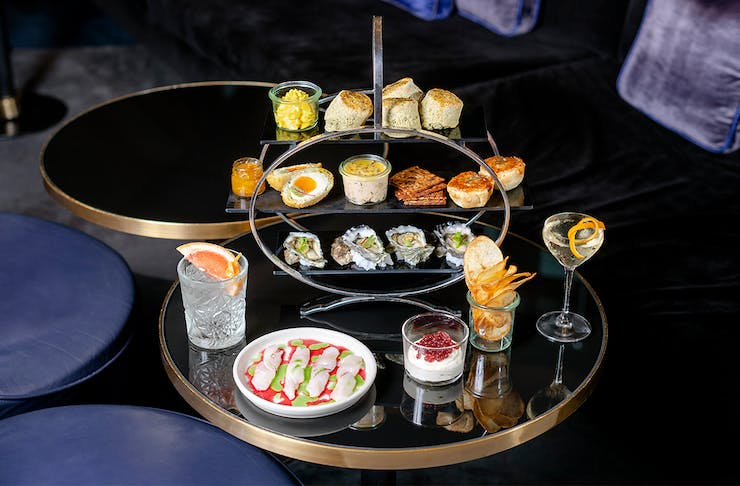 a tray filled with high tea bites with cocktails next to it