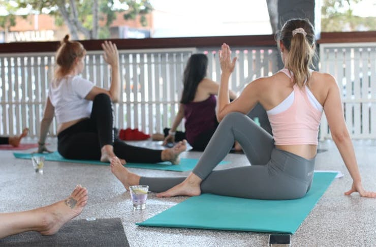 people doing yoga with glasses of gin beside them
