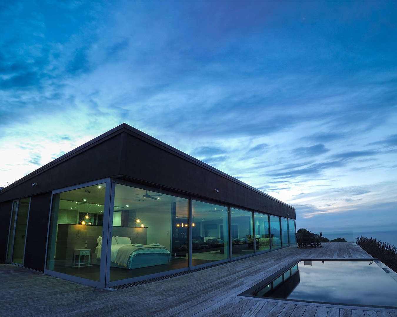 The outside of the lovely glasshouse, showing an infinity pool to the right under a sky at dusk.