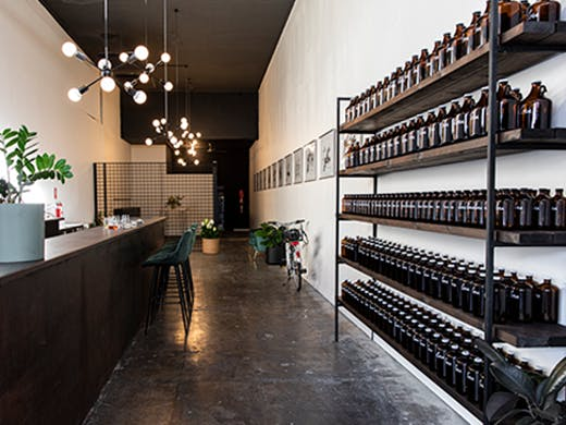 A long, minimally-designed wine bar with bottles on the right hand wall.