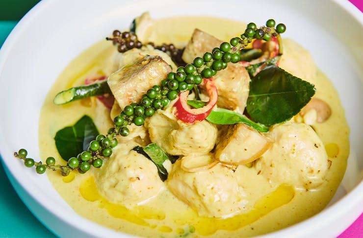 a bowl of green fish curry