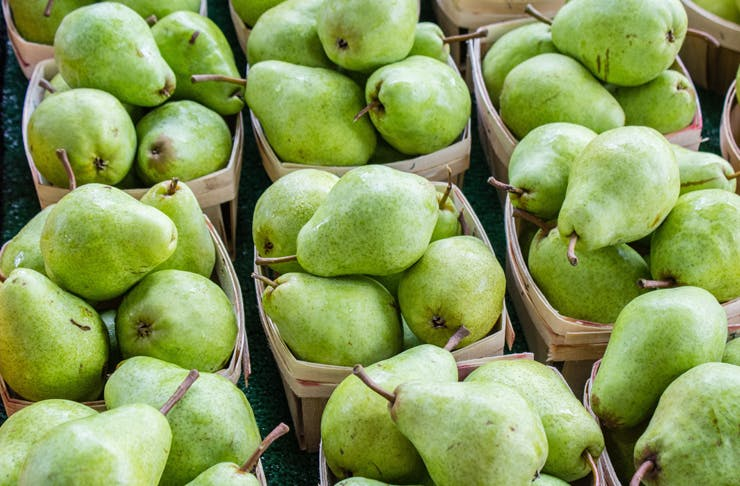 Small cardboard boxes filled with fresh pears.