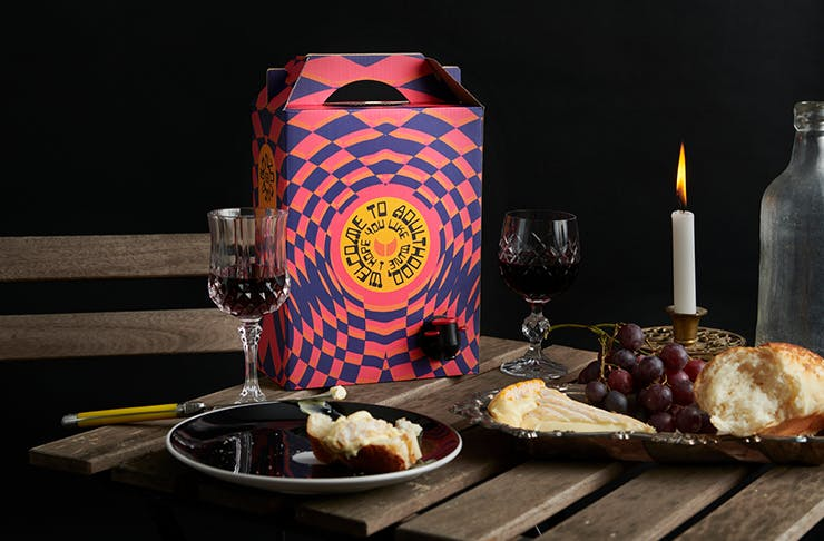 A colourful box of cask wine on a table next to a plate of cheese and ornate wine glasses.