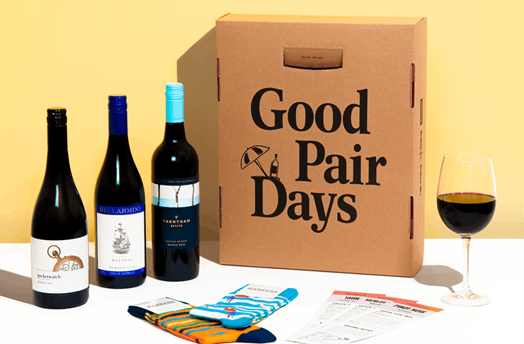 Three bottles of wine next to three pairs of socks and a box with the words