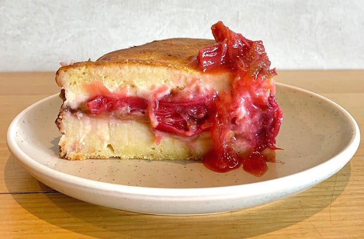 A decadent slice of rhubarb pudding on a white plate.
