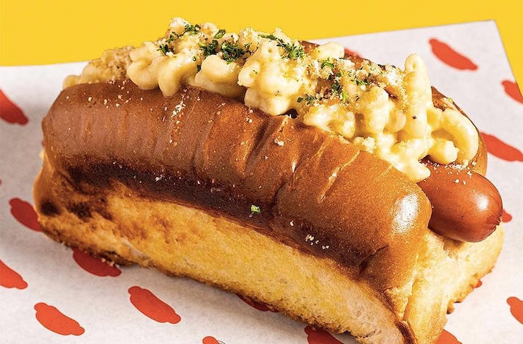 A mac 'n' cheese hot dog from GOOD DOG BAD DOG sits on a plate looking delicious.