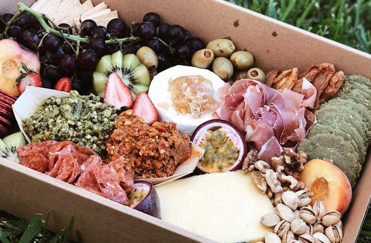 A gourmet picnic platter box, filled with cheeses, crackers, fruit, meats and nuts.