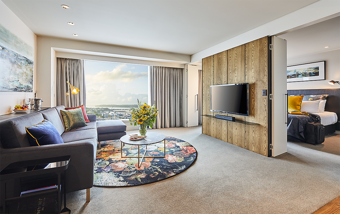 A room at The Grand By SkyCity Hotel showing a comfortable living area with a luxury bedroom in the background.