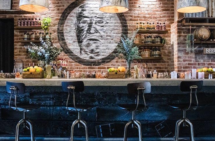 bar inside granddad jacks, with stools and a brick wall behind