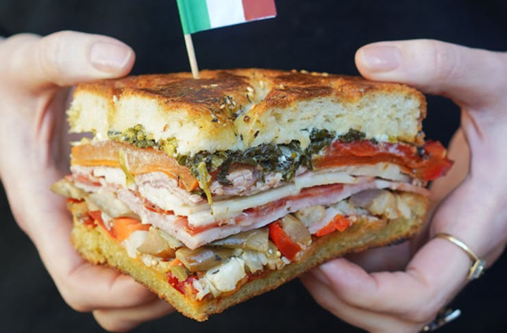 A stacked ham sandwich held in two hands
