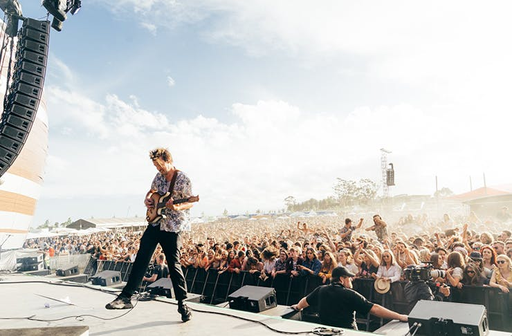 A man playing guitar on a stage at a festival.