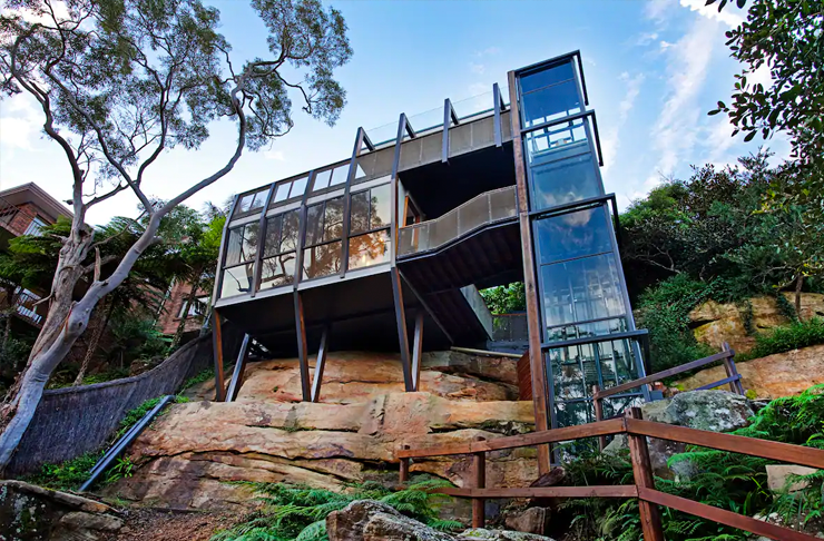 A glass treehouse built on a rocky cliff.