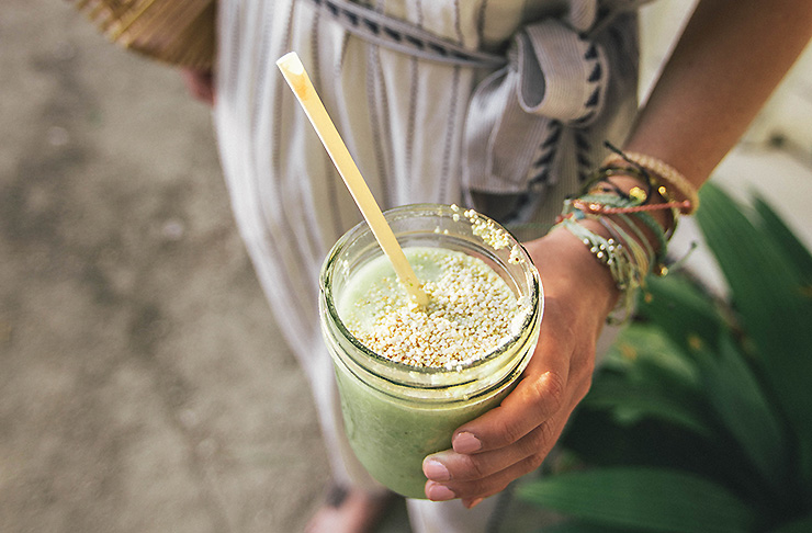 A woman wearing bracelets holds a glass containing a green smoothie with a straw sticking out of the top.