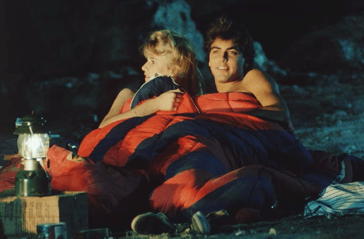 A young George Clooney and Laura Dern laying in a sleeping bag at night, on the set of 'Grizzly 2. Revenge'.