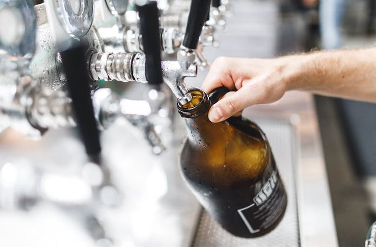 A growler being refilled at a row of beer taps