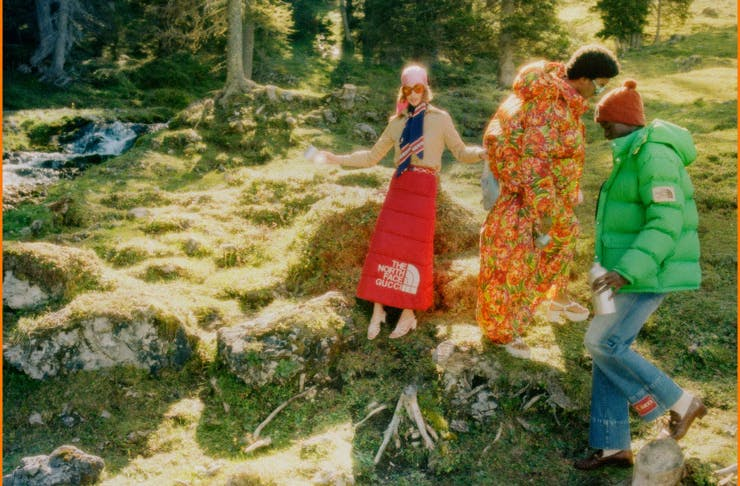 Three people dressed in The North Face x Gucci on a grassy hill.
