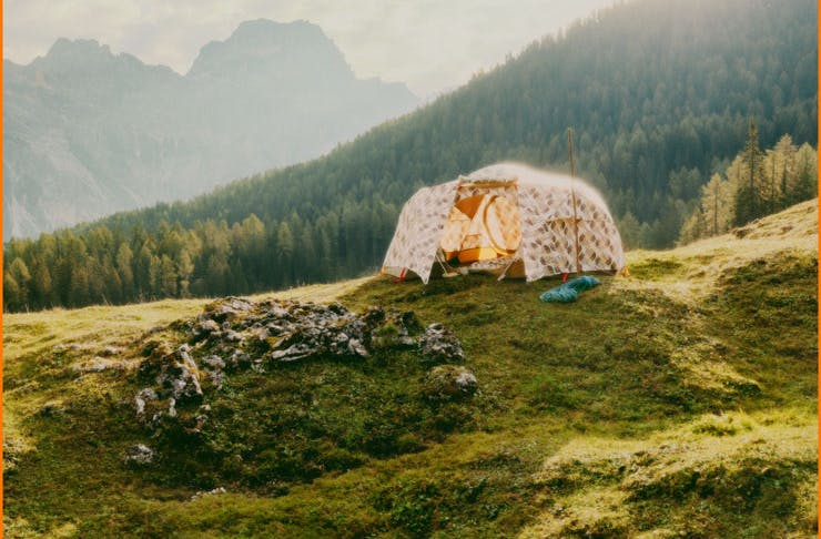 A tent on a grassy hill in the Alps.
