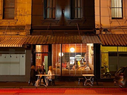 A small bar on a neon lit street.