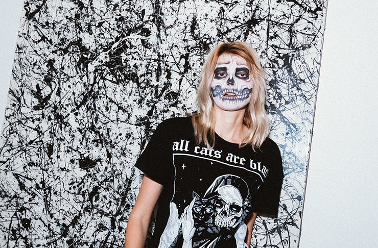 A woman with her face painted like a skull standing against a black-and-white painting.
