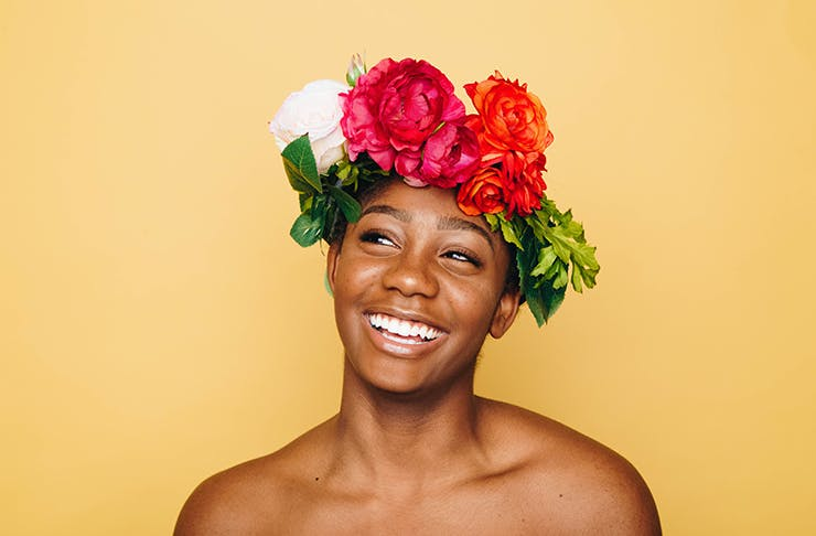A person standing in front of an orange wall with a big smile on their face and flowers in their hair.
