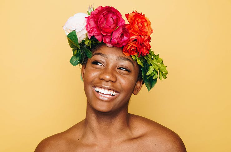 A girl with great skin and colourful flowers on her head beams off camera.