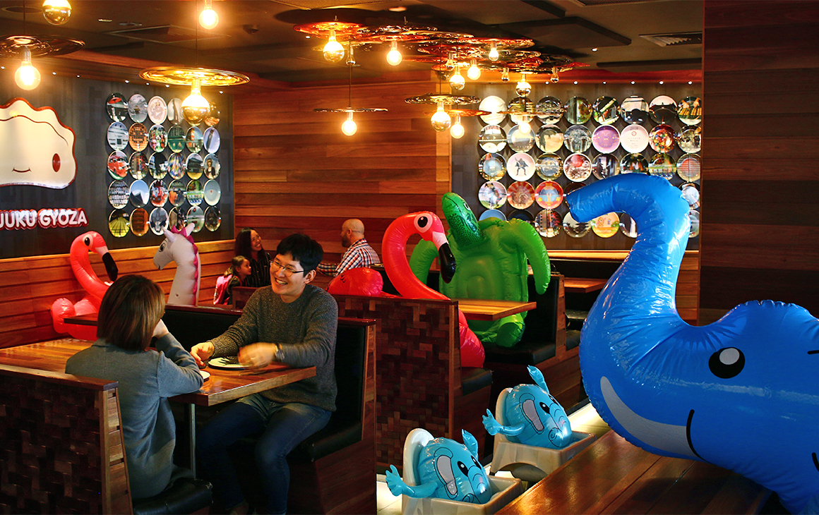 A restaurant with people at some tables, and inflatable animals at other