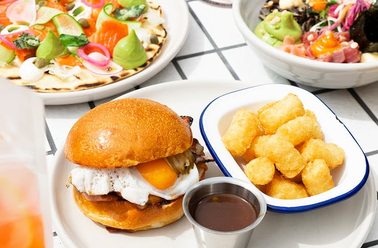 A burger, chips and salad sitting on white tiles.