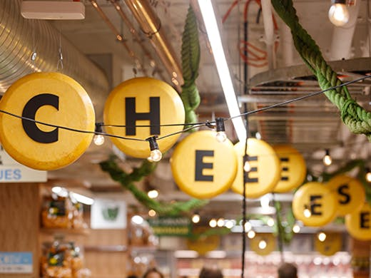 sign hanging from a ceiling saying 'cheese'