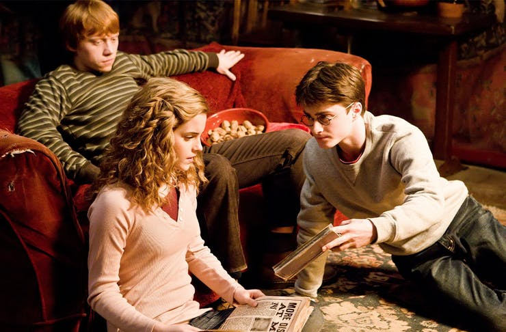 A scene from harry potter, with ron, hermione and harry sitting on a couch