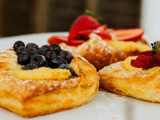 three pastries sit on a white tray.