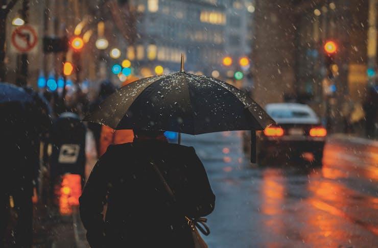 A man holding an umbrella on a dark, rainy day.