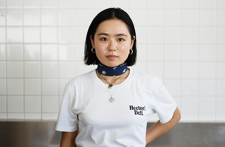 A woman wearing a white t-shirt with black text on it that reads