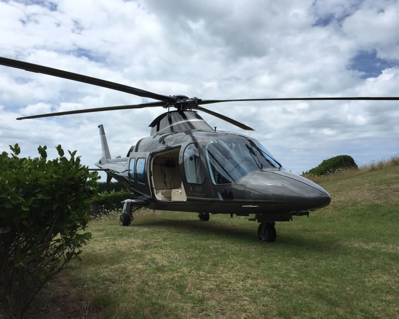 A helicopter parked on grass outside Mudbrick Winery