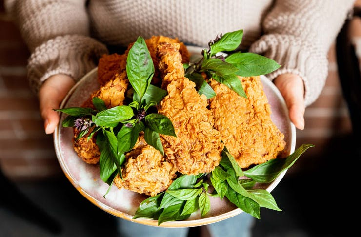 A plate of Hello Auntie's pho fired chicken, on a bed of basil leaves.