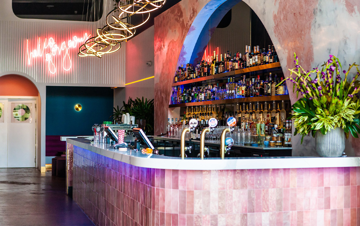 Very classy Hello Gorgeous bar with pink stone/marble looking walls and bar