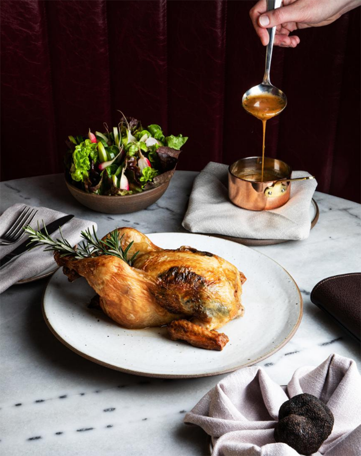 A fresh-roasted chicken next to a truffle in a hand-towel.