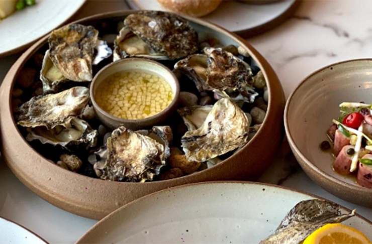 A plate of Sydney Rock oysters with a small bowl of apple vinaigrette in the centre.