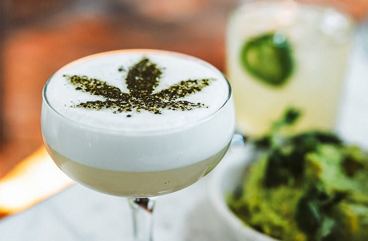 a cocktail with a cannabis leaf design sprinkled on top