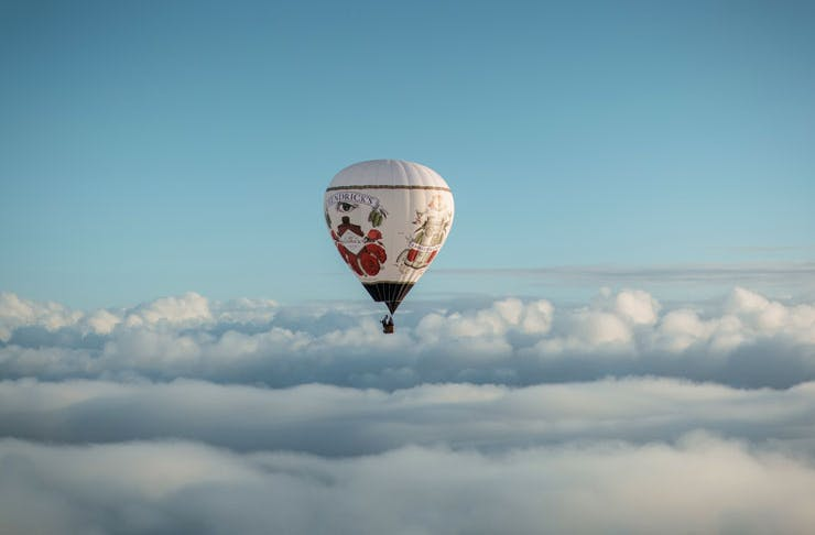 The Hendricks Hot Air Balloon Bar in flight over some clouds.