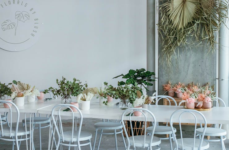 Long White table decorated with pink and white pot plants at Florals By Blush
